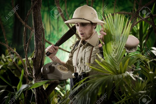 Young explorer with machete finding a vintage telephone in the jungle.